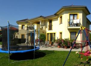 Zahrada s trampolínou a dětskými houpačkami